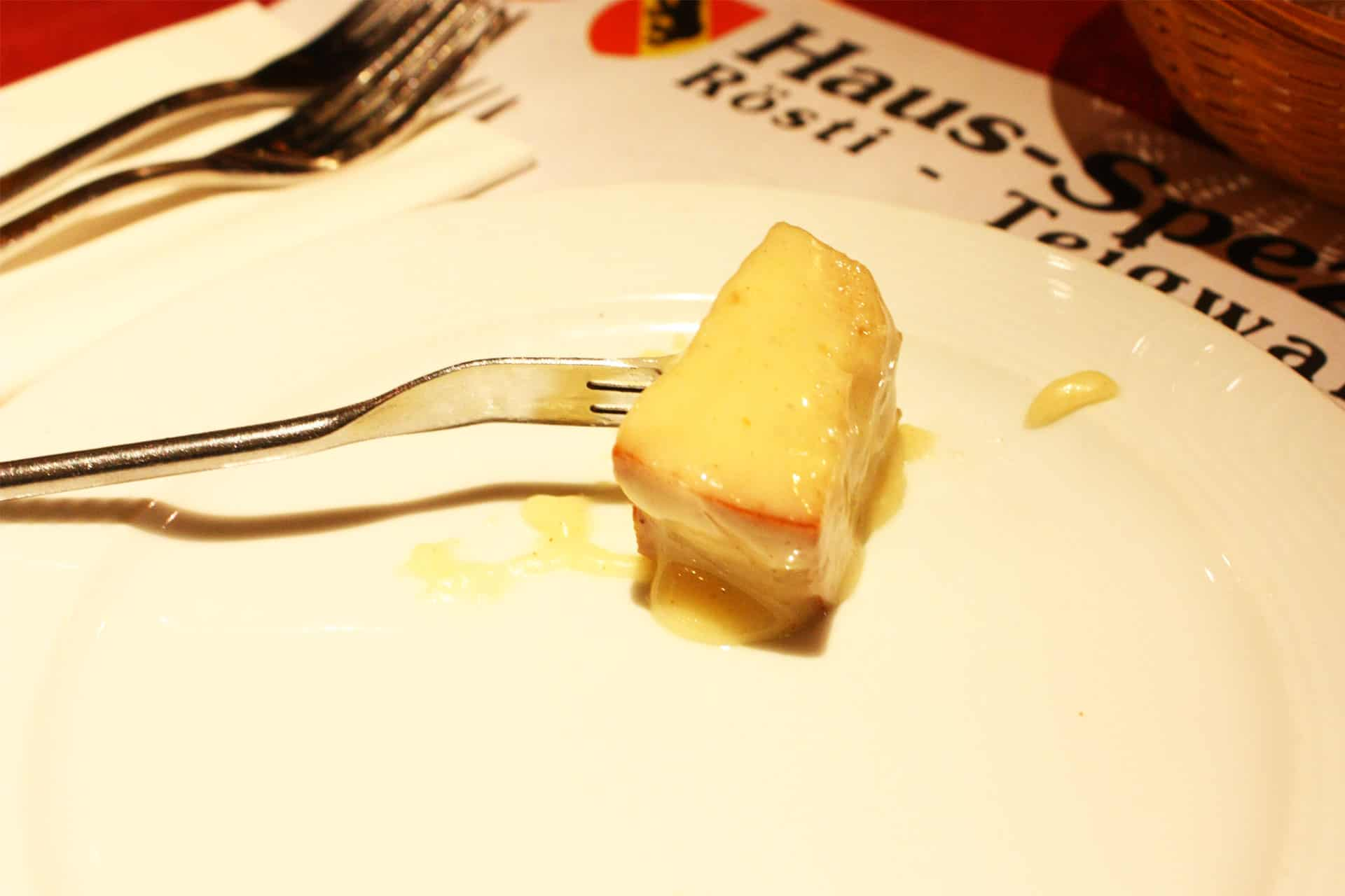 Using a long fork to coat the bread and put it onto own plate is the right etiquette when eating Swiss Fondue!